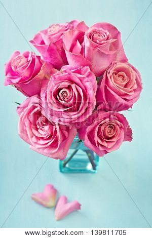 Beautiful fresh roses flowers in a vase on a blue background.