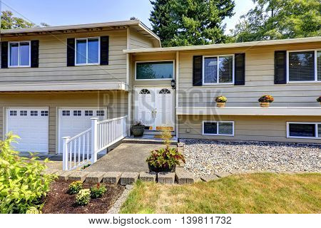 Beige siding house exterior with white trim. View of two garage spaces. White double front door with lantern