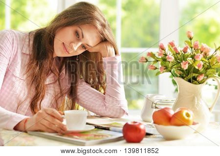 young woman with magazine and tea at home