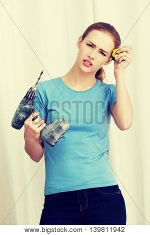 Beautiful caucasian woman holding drill.