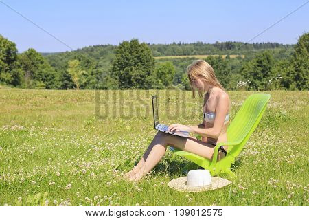 Young woman with laptop relaxing in chaise lounge