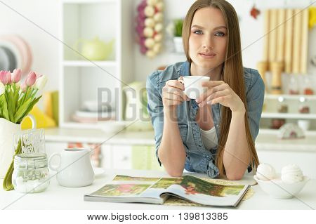 Smiling young beautiful woman   with magazine at kitchen