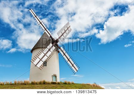 ancient european windmill restored on the top of a hill