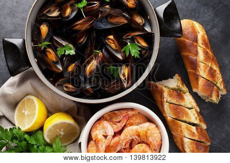 Mussels and shrimps on stone table. Top view