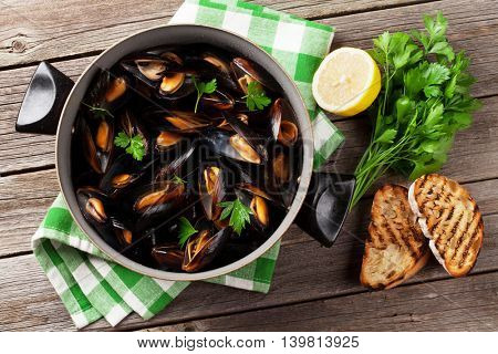 Mussels and bread toasts on wooden table. Top view