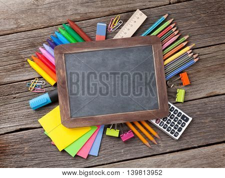 Chalk board for your text over colorful supplies. Back to school concept with copy space