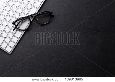 Office desk with pc and glasses over leather texture. Top view with copy space