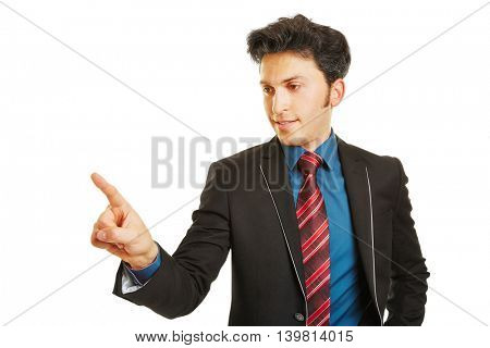 Business man reaching with his index finger for a virtual menu on a touchscreen