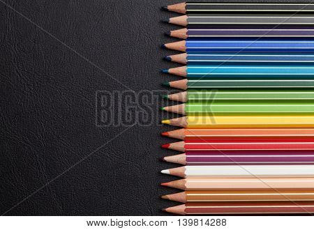 Colorful pencils over leather desk table. Top view with copy space
