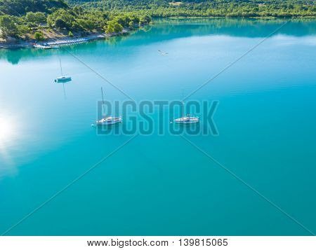 Beautiful aerial view of three yachts sailing on azure water. Coastal shore on background