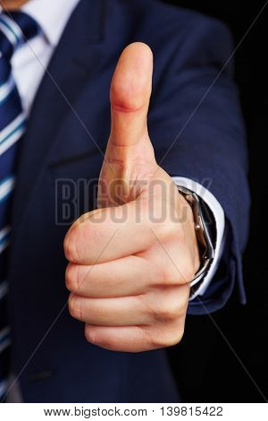 Thumbs up symbol from a business manager on a dark background
