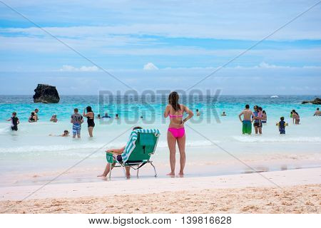 HORSESHOE BAY BERMUDA - MAY 26 - An attractive lady in a pink bikini overlooks the pristine aqua marine colored water of Horseshoe Bay on May 26 2016 in Bermuda.