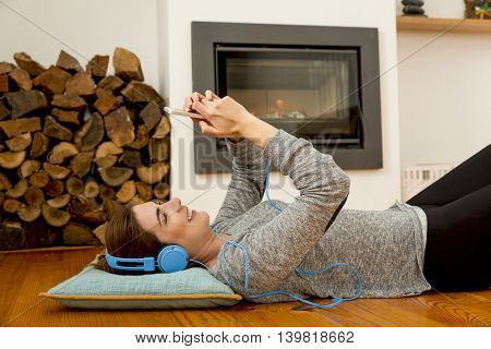 Beautiful woman lying on the floor and listen music