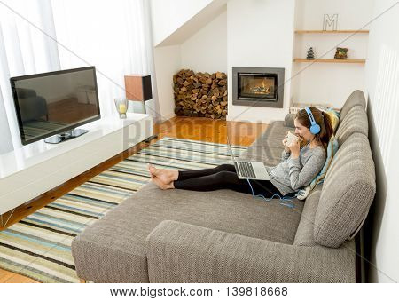 Beautiful woman working at home with a laptop while listen music and drinking coffee