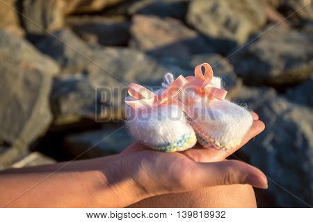 Pregnant woman holding newborn baby shoes in hand