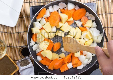 Chef stir-fried vegetable in the pan for cooking Japanese pork curry / cooking Japanese pork curry concept