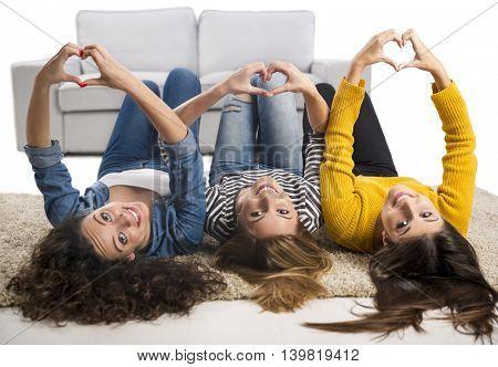 Happy teen girls at home lying in the floor