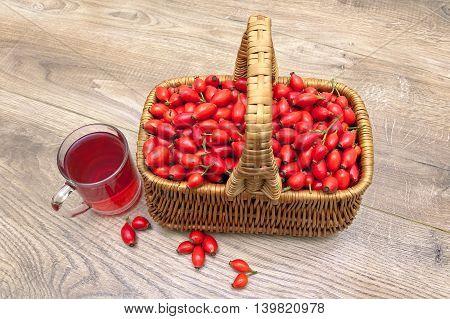 ripe rosehip berries in a basket on a wooden background. horizontal photo.