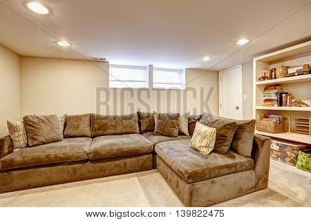 Spacious Family Room With Large Corner Sofa And Bookcase.