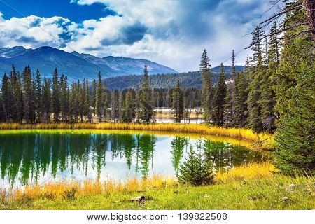 Autumn day in Jasper National Park in the Rockies of Canada. Shallowed circular lake in the autumn forest
