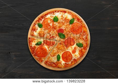 Delicious italian vegetarian pizza Margherita with tomato and cheese, thin pastry crust and one piece cut. Fast food top view at wooden desk on black wood table background