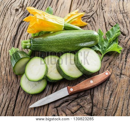 Zucchini with slices and zucchini flowers on a wooden table.