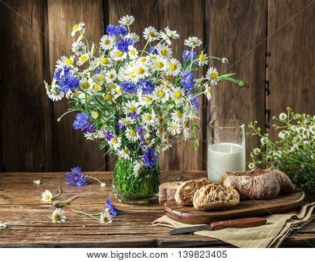 Bouquet of field flowers, glass of milk and soft bread on the wooden table.