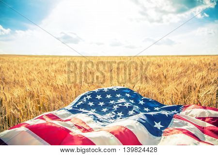 USA American flag lies on the golden wheat field. Toned Image.