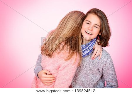 Portrait of happy teenage boy and girl standing together over pink background. Friendship. First love.