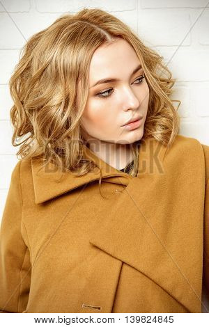 Young fashion woman. Beautiful blonde girl posing in studio in mustard-colored coat. Beauty, fashion.