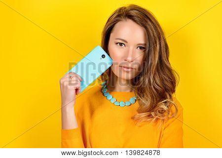Smiling young woman posing with her  smartphone over yellow background. Beauty, fashion. Modern telecommunications.