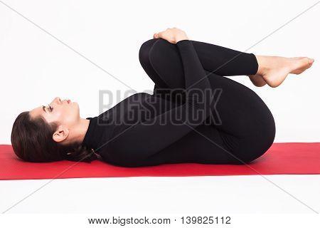 Beautiful athletic girl in black suit doing yoga. apanasana asana apan pose. Isolated on white background.