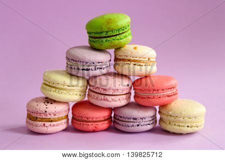 Tasty colorful macaroons on purple background