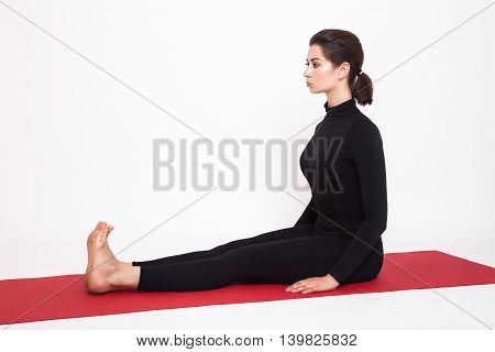 Beautiful athletic girl in a black suit doing yoga. dandasana asana - plow pose . Isolated on white background.