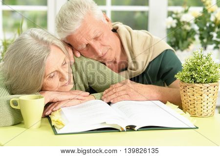 Senior couple  sleeping  with book at home