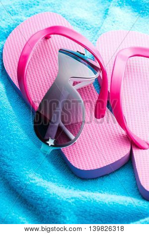 Flip flops and sunglasses on blue towel.