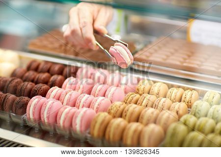 Sellers hand taking out macaroni from glass case