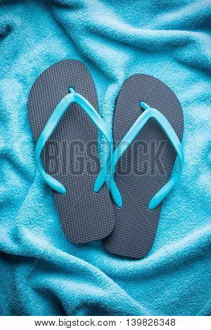 Flip flops on blue towel.