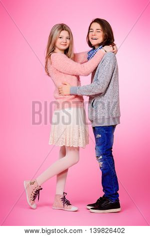 Full length portrait of happy teenage boy and girl standing together over pink background. Friendship. First love.