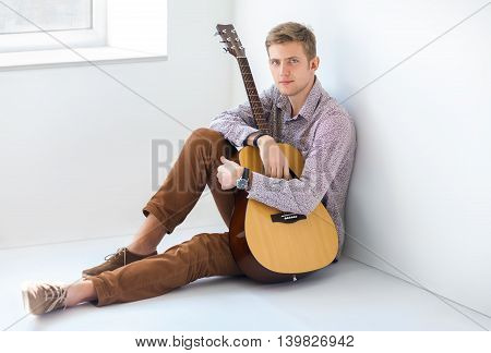 Portrait Of Handsome Man With Guitar Siting On Floor