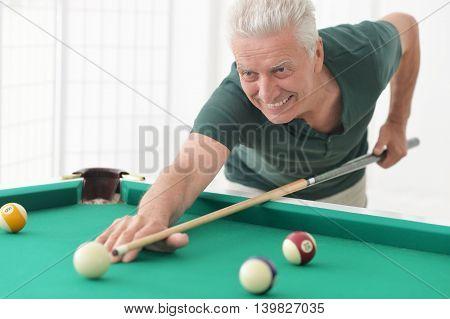 Portrait of a mature man Playing billiard