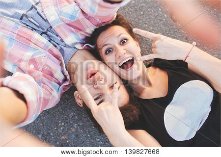 Excited young people lying down. Teenager pair doing a selfie while lying on road. Top view.
