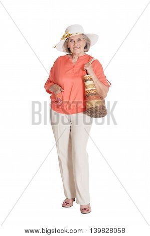 Portrait of beautiful senior woman in hat and bag on white background