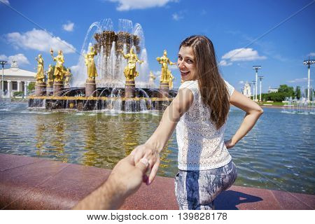Follow me. Young happy woman pulls the guys hand on the Fountain of friendship of the people
