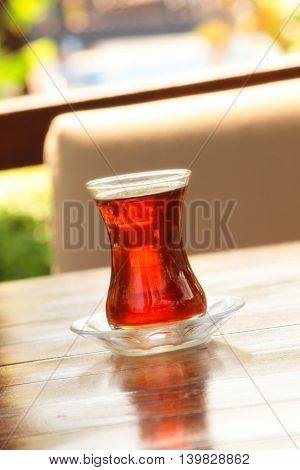 A glass of hot Turkish tea on a wooden table