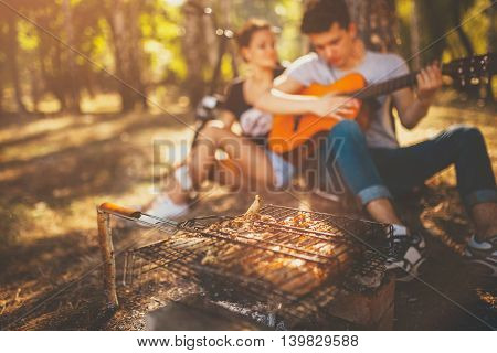 Picnic. Grilling meat and playing guitar. Defocused background. Teenagers loving boy and girl sitting together by a tree on weekend sunny day.