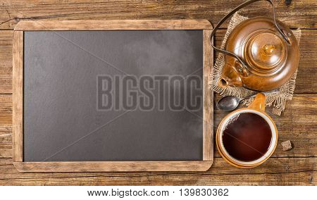 Top view of teapot cup of hot tea and old blackboard on rustic wooden background copy space for menu.