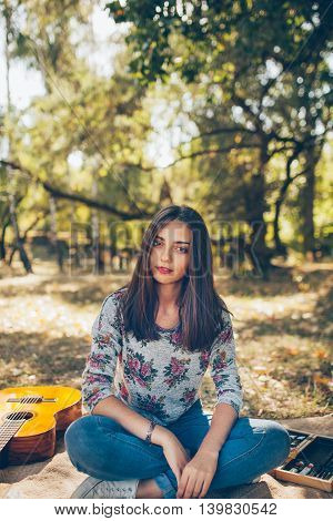 beautiful teenage girl wearing casual clothes sitting outdoors in forest. Cute hipster brunette young woman with guitar on autumn day