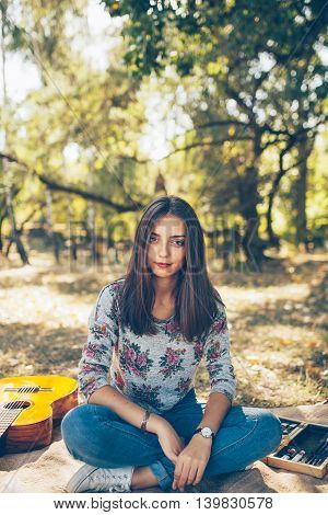 Adorable teen girl wearing casual clothes sitting outdside in forest. Cute hipster brunette young woman with guitar on autumn day