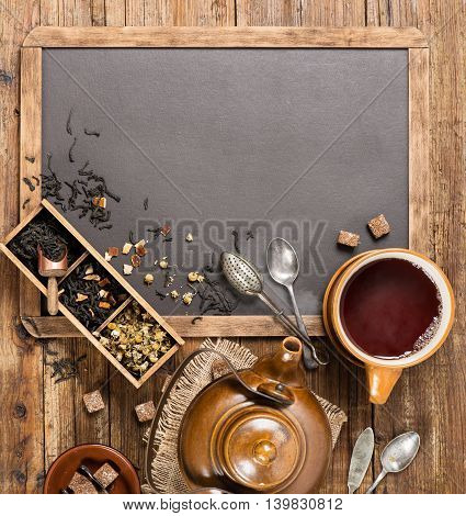 Top view of assortment of fragrant dried teas and Cup of tea with teapot on a blackboard with copy space for your text.
